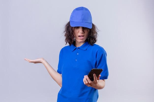 Fille de livraison en uniforme bleu et capuchon regardant téléphone mobile avec expression confuse debout avec bras levé sur blanc