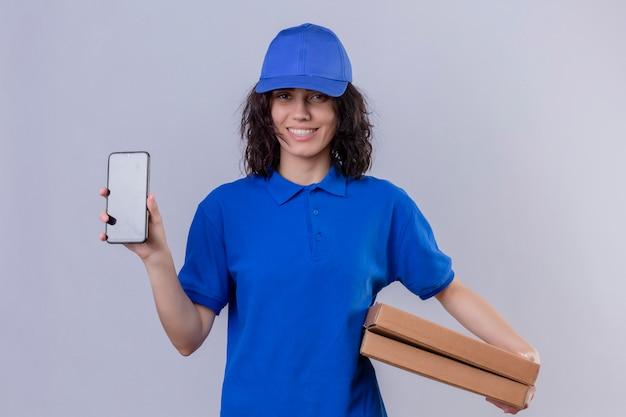 Fille de livraison en uniforme bleu et chapeau tenant des boîtes à pizza montrant un téléphone mobile souriant sympathique debout sur blanc