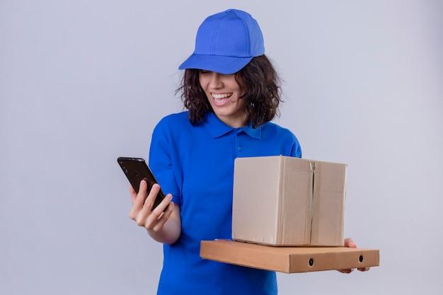 Fille de livraison en uniforme bleu et chapeau tenant des boîtes à pizza et paquet de boîte regardant l'écran du téléphone mobile souriant avec un visage heureux debout sur blanc