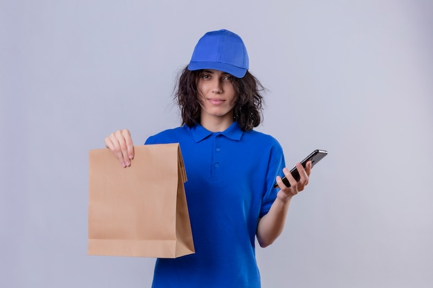 Fille de livraison en uniforme bleu et chapeau tenant un paquet de papier et un téléphone mobile avec une expression sérieuse et confiante debout sur blanc