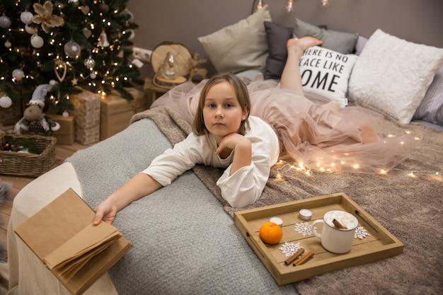 Fille avec un livre au lit, petit déjeuner au lit, flou artistique