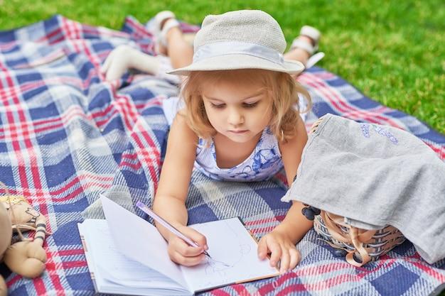 Fille avec un livre dans le parc sur un pique-nique