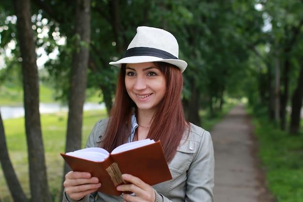 Fille avec livre dans le parc