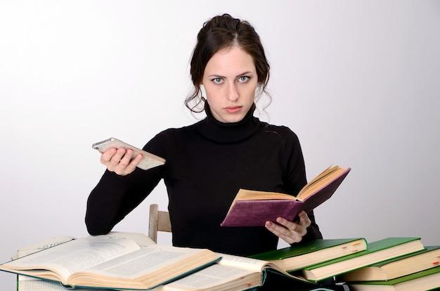 Fille livre examen difficultés pull noir enseigne à la table fatigué se réjouit des émotions