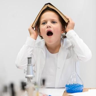 Fille avec livre de science sur la tête