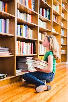 Fille avec des livres assis sur les étagères