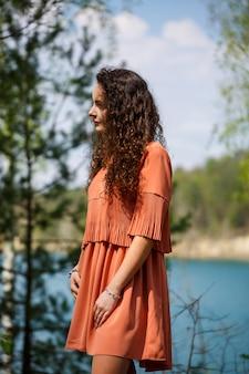 Une fille avec de longs cheveux bouclés ondulés dans ses cheveux fleurs tissées dans une robe en guipure transparente blanche pieds nus en été sur la nature dans une forêt au coucher du soleil debout près de la route et des buissons