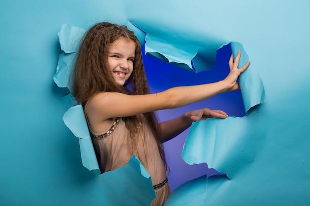 Fille lorgnant à travers un trou dans du papier bleu