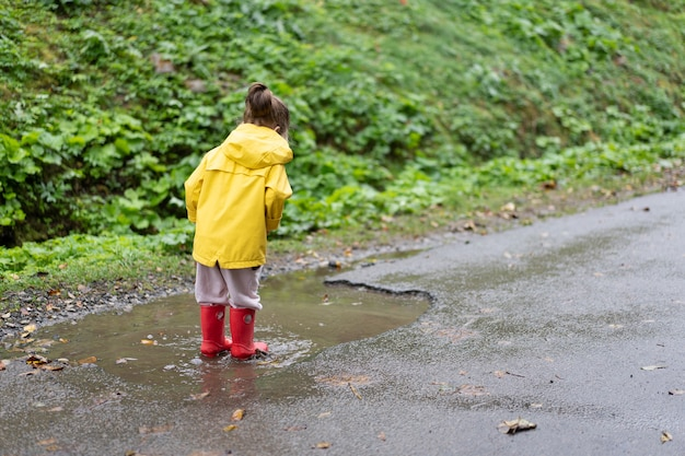 Fille ludique portant un imperméable jaune en sautant dans une flaque d'eau pendant la pluie bonne enfance