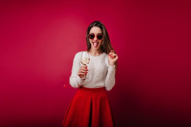 Fille ludique avec verre à vin debout et posant avec la langue