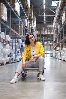 Fille avec des lunettes, assis sur un panier dans un magasin dans l'entrepôt