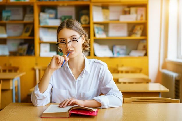 Fille avec des lunettes, assis à une table avec un livre dans la salle de classe