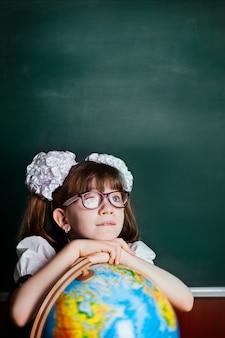 Une fille à lunettes au bureau de la classe est en train de rêver.
