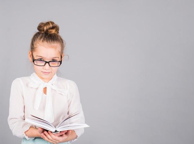 Fille à lunettes debout avec livre