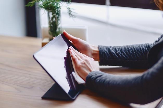 La fille à lunettes essuie l'écran de la tablette près de la table
