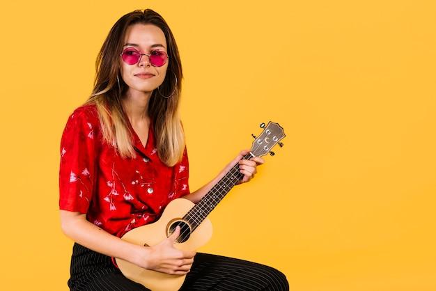 Fille à lunettes jouant de l'ukelele