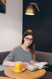 Fille à lunettes en lisant un livre dans un café