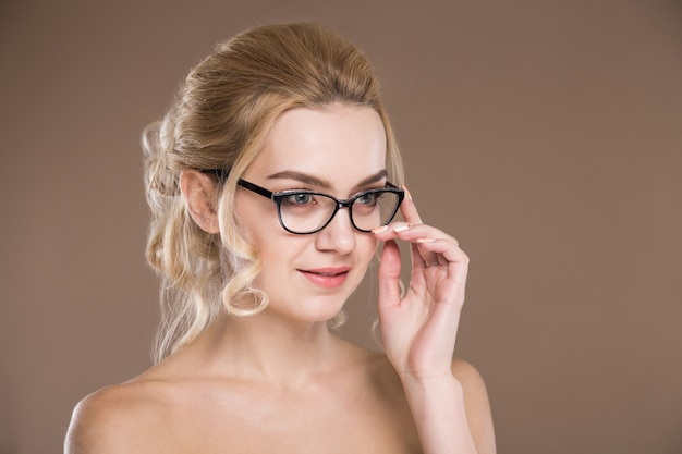 Fille avec des lunettes avec la main près du visage