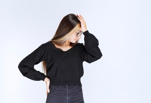 Une fille à lunettes a mal à la tête.