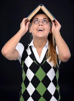 La fille à lunettes met un livre sur sa tête.