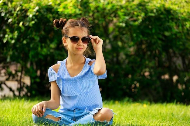 Une fille à lunettes noires assise sur l'herbe en été. photo de haute qualité