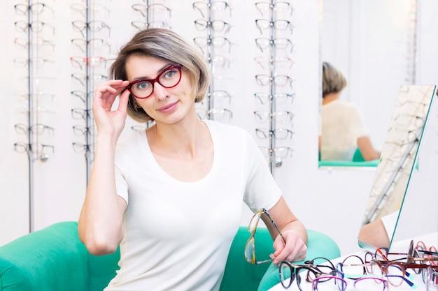 Fille à lunettes pour la vue. essayer des lunettes dans un magasin d'optique. fille satisfaite