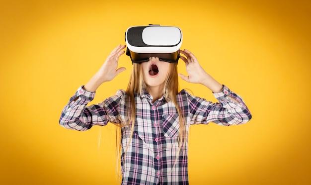 Fille avec des lunettes de réalité virtuelle sur un mur jaune