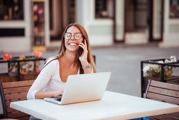 Fille avec des lunettes de rire tout en parlant sur le smatphone. assis avec un ordinateur portable dans le café en plein air.