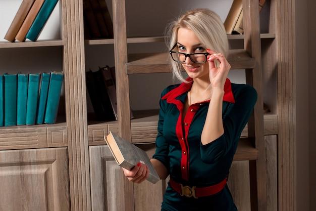 Fille avec des lunettes et une robe bleue tenant un livre dans leurs mains