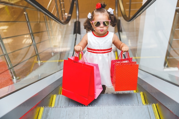 Fille à lunettes de soleil sur l'escalator dans le centre commercial avec des achats