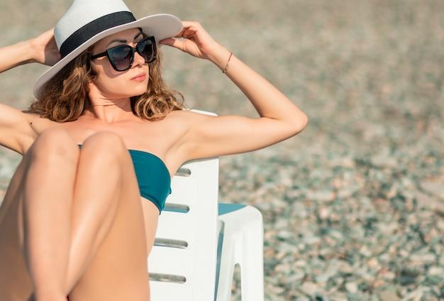 Fille de lunettes de soleil mode de vie heureux bronzée sur un transat. belle femme bikini européenne reposant sur la vue de vacances au coucher du soleil. mode de vie sain.
