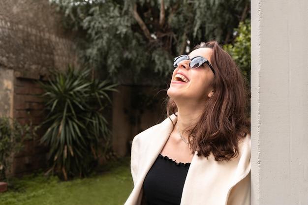 Fille avec des lunettes de soleil sombres en levant et en riant
