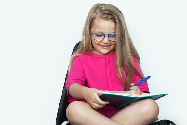 Fille à lunettes souriant dans un fauteuil tout en tenant un livre sur un mur blanc avec espace libre
