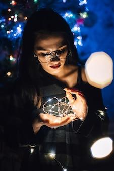 Fille avec des lunettes tenant une guirlande de lumières la nuit