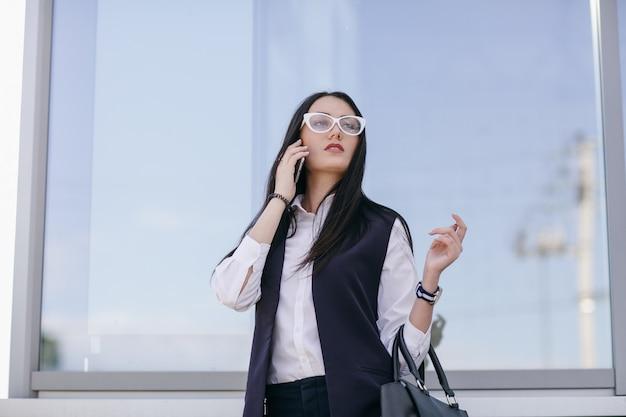 Fille avec des lunettes transparentes parler sur le mobile
