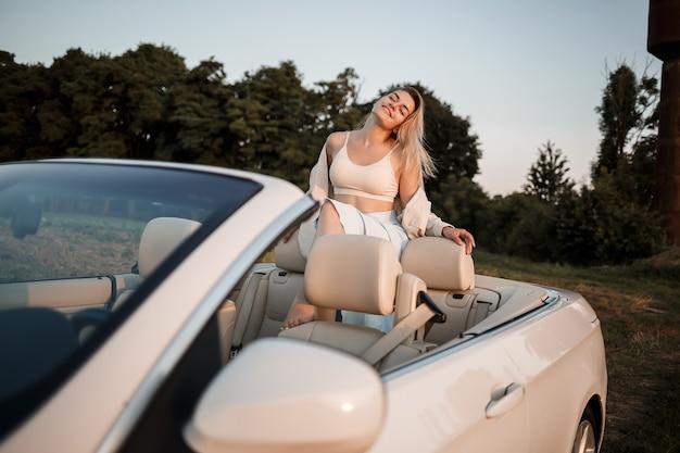 Une fille de luxe glamour aux cheveux blonds souriante assise sur une décapotable blanche. jeune femme réussie s'asseyant dans sa voiture blanche