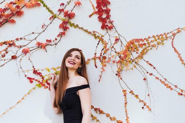 Fille magnifique aux cheveux longs en riant dans une robe noire se promenant dans son jardin, posant contre le mur