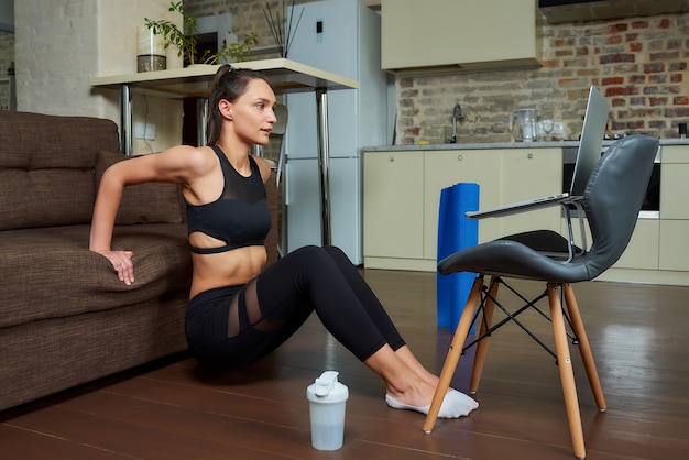 Une fille maigre dans un costume moulant noir fait des exercices de triceps et de poitrine et regarde une vidéo d'entraînement en ligne sur un ordinateur portable. une entraîneure dirige un cours de fitness à distance à la maison.
