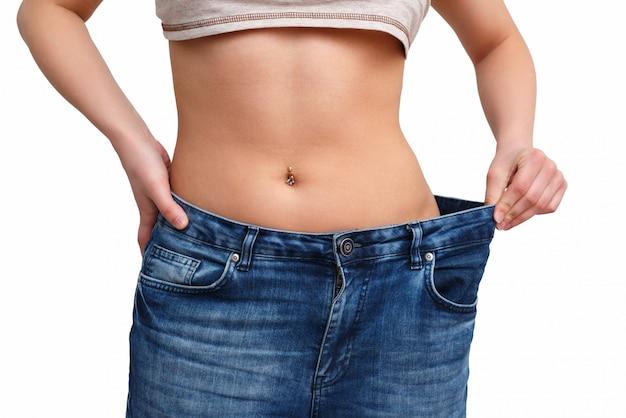 Fille maigre en gros pantalon - concept de perte de poids. isolé sur un espace blanc
