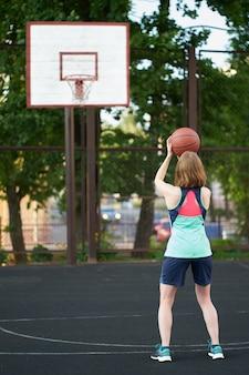 Fille maigre rousse lancer une balle dans un panier de basket en plein air