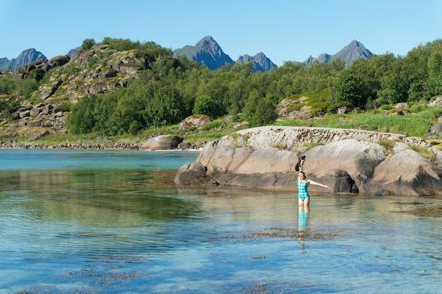 Une fille en maillot de bain avec un appareil photo se tient dans l'eau transparente turquoise de la baie, l'île d'arsteinen, l'archipel des lofoten, norvège