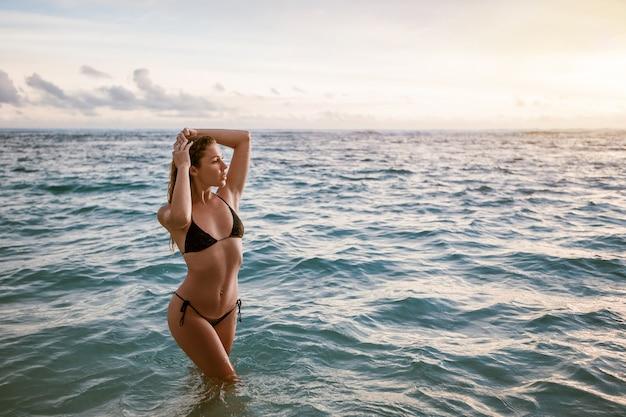 Fille en maillot de bain bikini posant dans l'océan au coucher du soleil