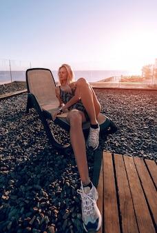 Fille en maillot de bain fermé sur une chaise longue sur le fond de la mer rencontre l'aube, se détendre et profiter de la mer et bronzer