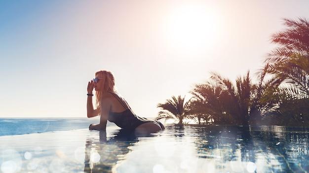 Une fille en maillot de bain fermé et lunettes de soleil sort de l'eau dans une piscine panoramique et aime bronzer. concept de vacances.