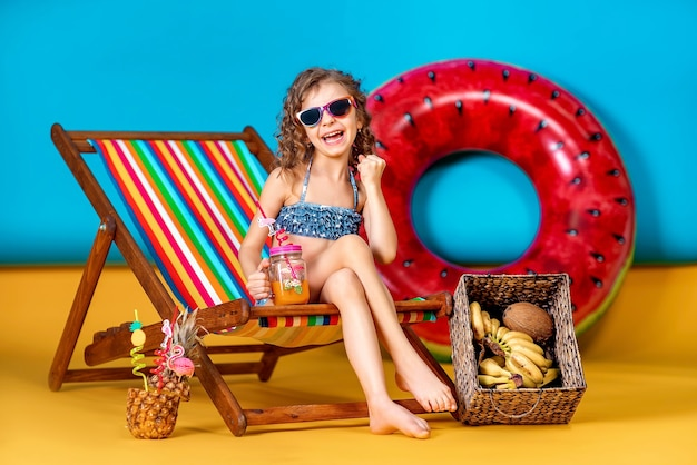 Fille en maillot de bain et lunettes de soleil assis dans une chaise longue arc-en-ciel