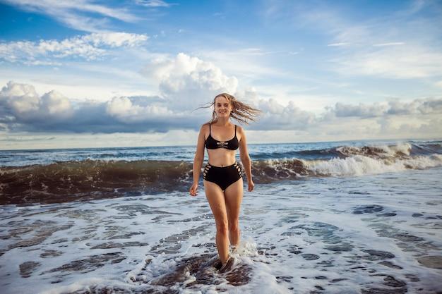Fille en maillot de bain noir se promène le long de l'océan
