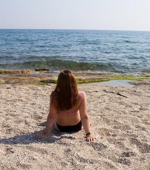 Fille en maillot de bain sur la plage au bord de la mer. femme rousse sur une plage de sable. des vacances dans le sud