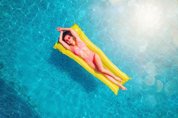 Fille en maillot de bain qui bronze dans une piscine