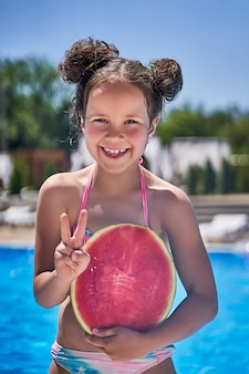 Fille en maillot de bain se dresse avec une pastèque sur la plage