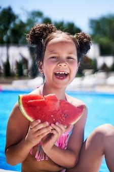 Fille en maillot de bain se tient avec une pastèque sur la plage.